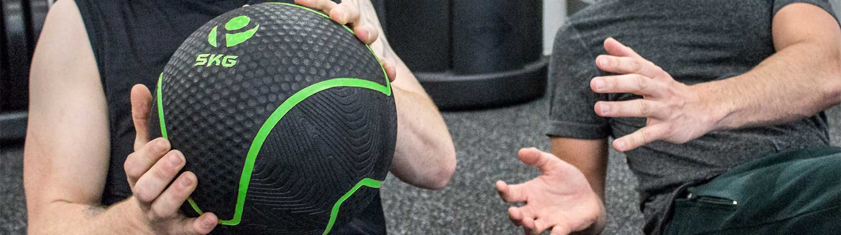 One person passing a weighted medicine ball to another person
